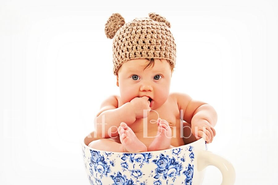 Baby girl wearing a teddy bear hat in teacup