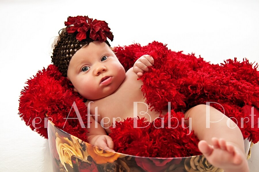 Infant covered in red shawl relaxing in floral teacup