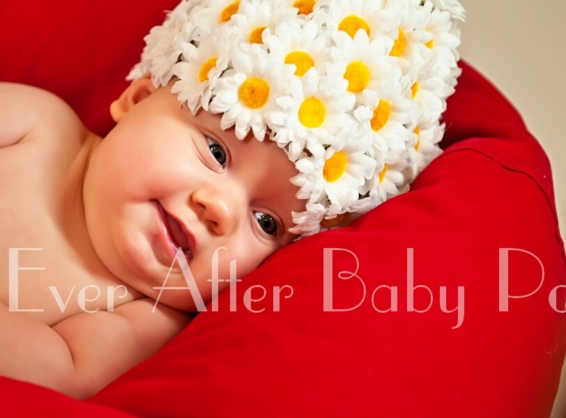 Infant in daisy hat reclining on red pillow.