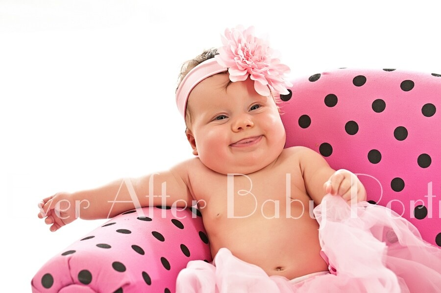Smiling four month old in pink tutu in polka dot chair.