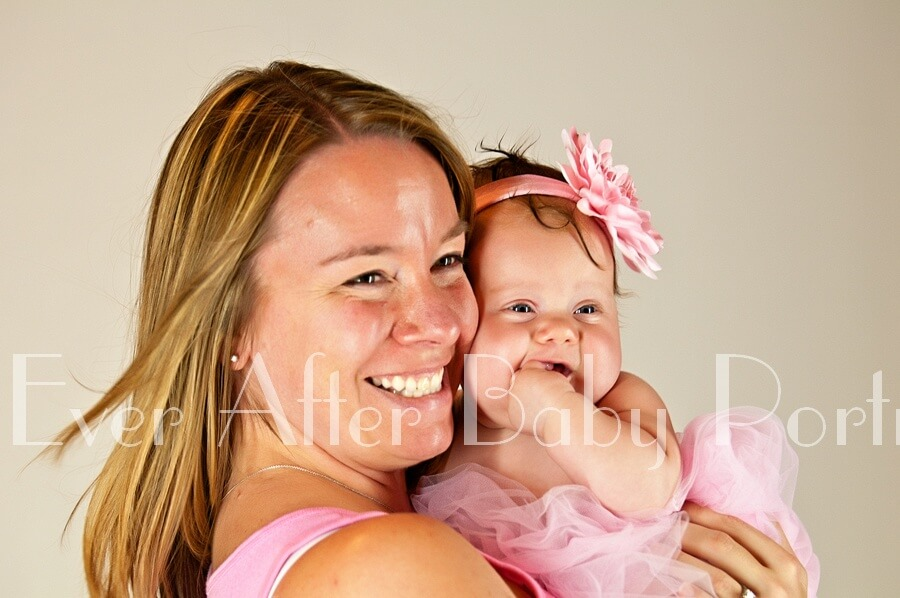 Mom and baby girl smiling for a closeup portrait.