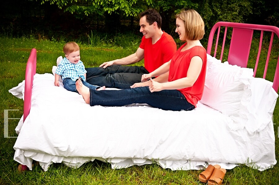 Family resting on red bed in outdoor studio.