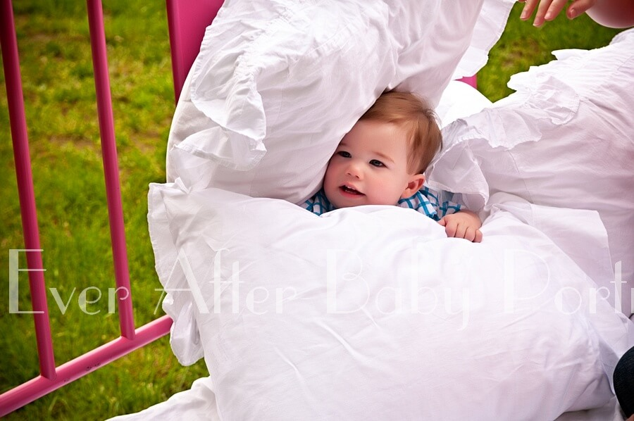 One year old playing with pillows on bed.