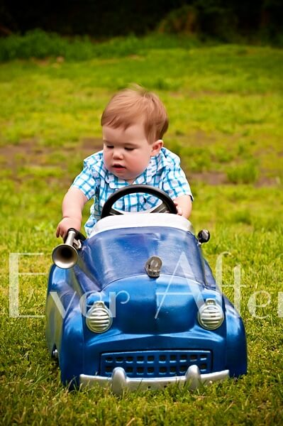 Little boy driving in blue toy car.