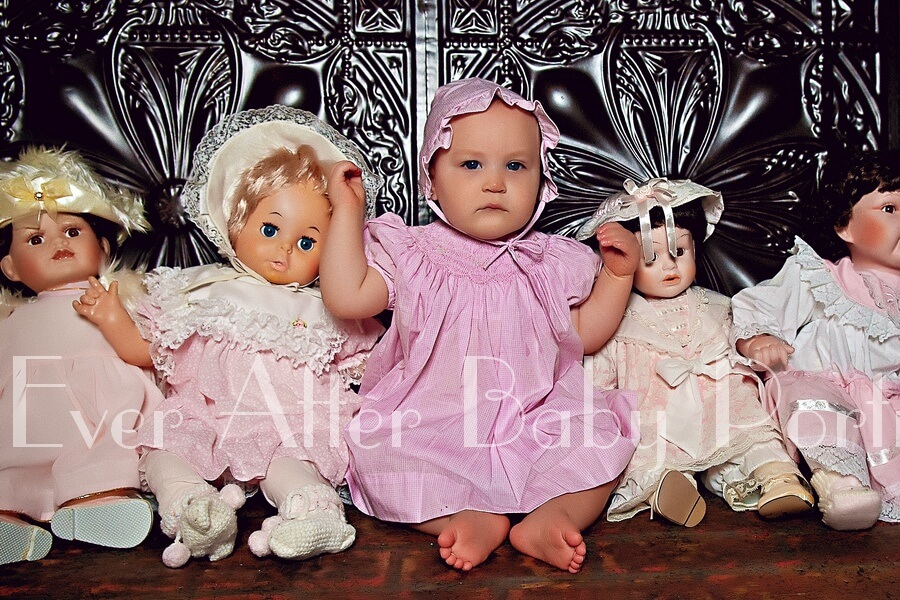 Baby dressed up in doll outfit.