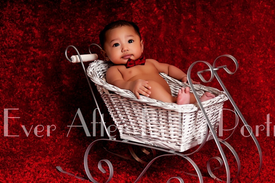 Baby with bow tie in white sleigh.