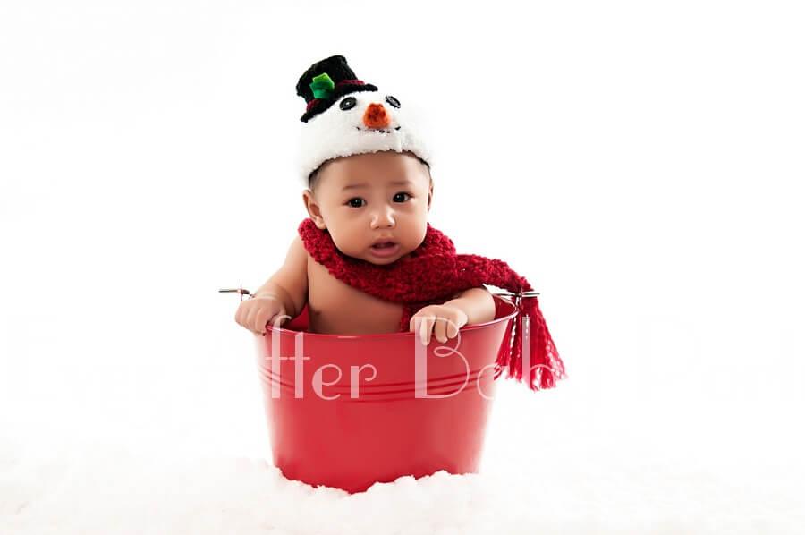 Baby boy in red bucket.