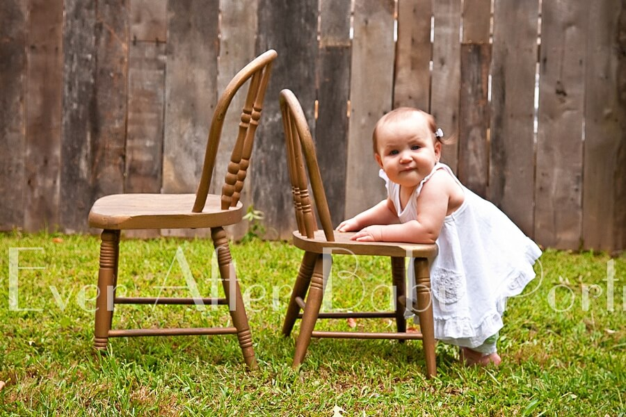 Little girl in white outfit leans against chair.
