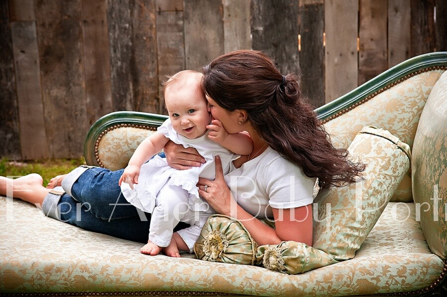 Mommy and baby on sofa for outdoor portrait.