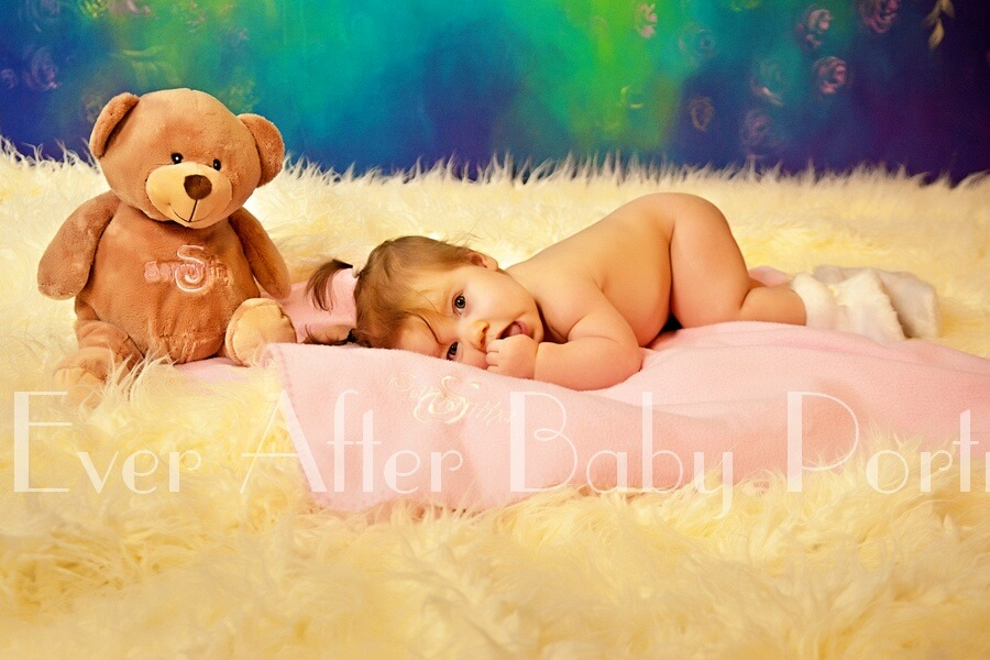 Baby resting on pink blanket with teddy bear.