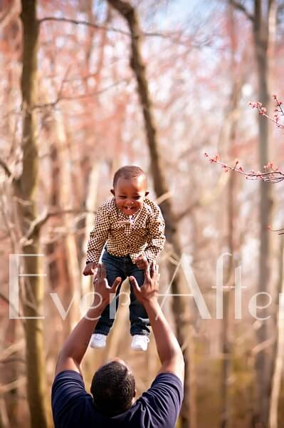Father holds one year old up high.