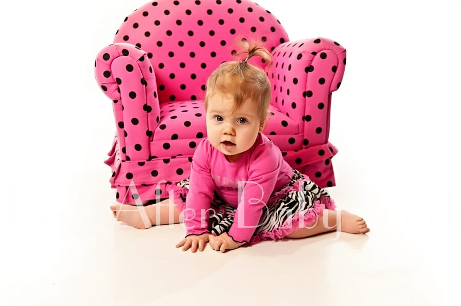 Little girl in pink with pink polka dot chair.