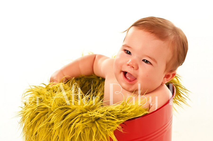 Laughing six month old in red bucket.