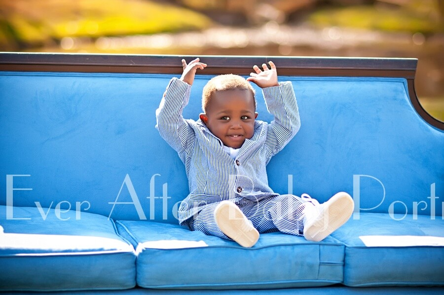 Toddler in pinstripe suit on blue sofa.