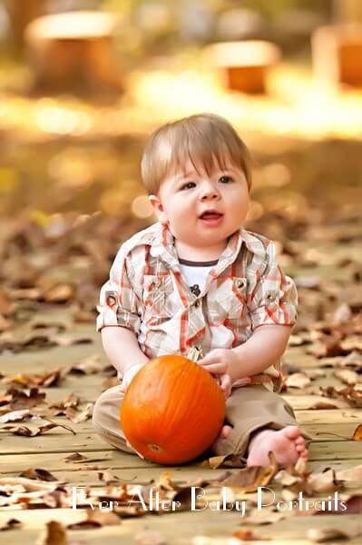 Baby boy on bridge with pumpkin.