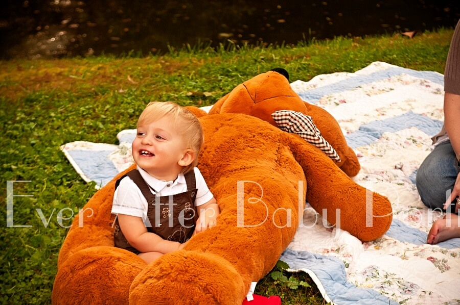 Baby boy and teddy bear in ourdoor image.