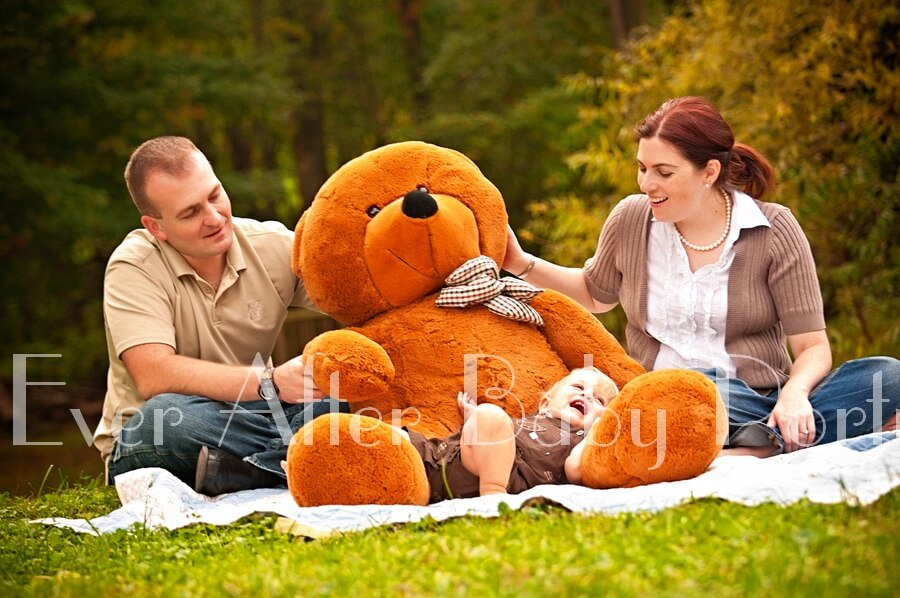 Baby relaxing on grass with teddy bear.