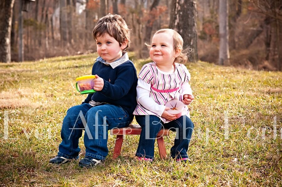 Little sister and brother sit on stool.