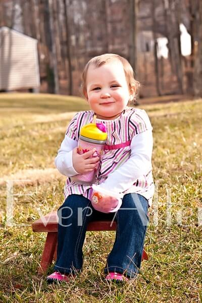 One year old girl enjoying snacks outside.