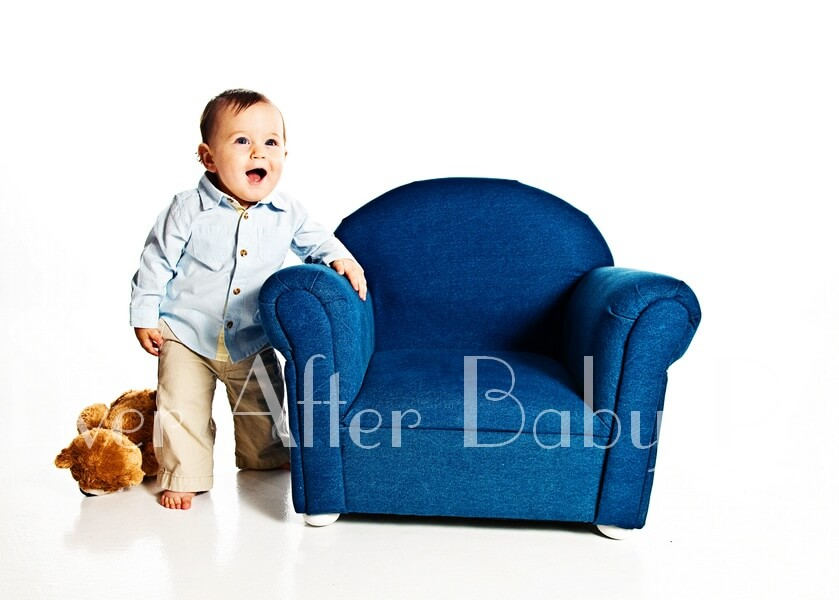 Toddler standing next to blue chair.