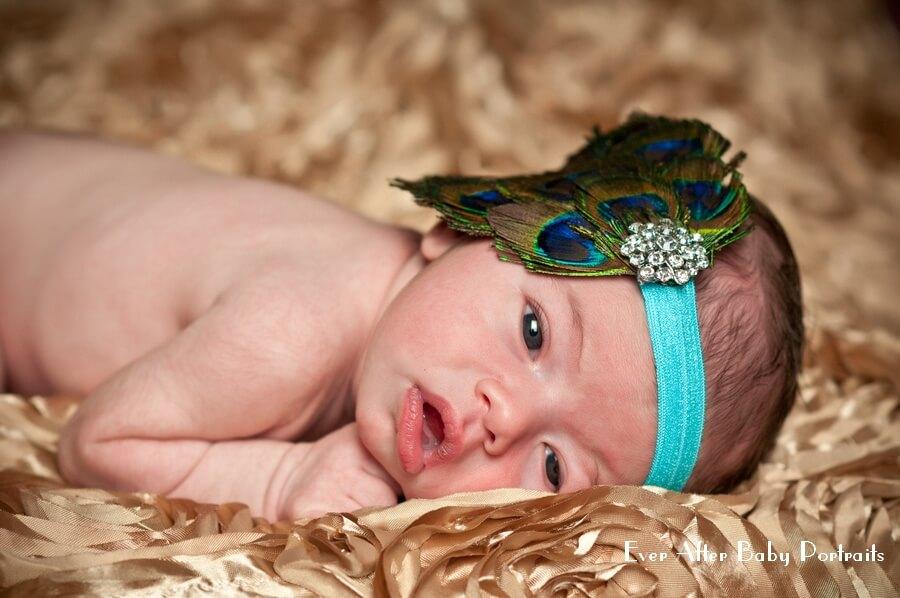 Wide eyed newborn on beige cloth.