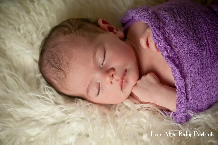 Sleeping newborn in purple blanket.